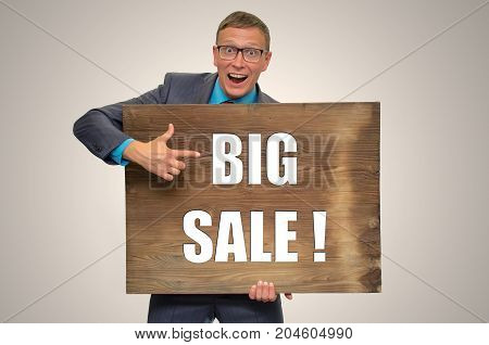 Mad Smiling man in suit and glasses holding in hands empty bill board with