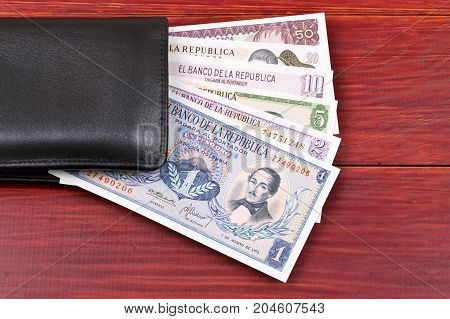Old Colombian money in the black wallet