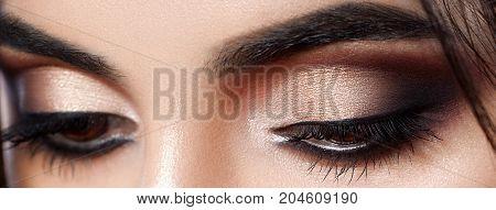 Closeup shot of woman eye with evening makeup. Long eyelashes. Smokey Eyes. Macro. Studio
