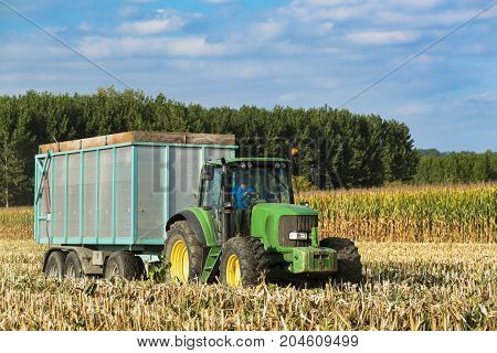 Tractor With Trailer In A Field Of Corn Threshed