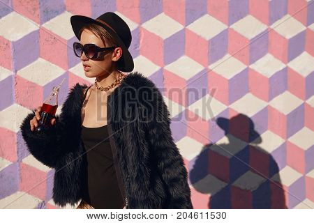 Young provocative woman in fur and sunglasses holding bottle of soda looking away.