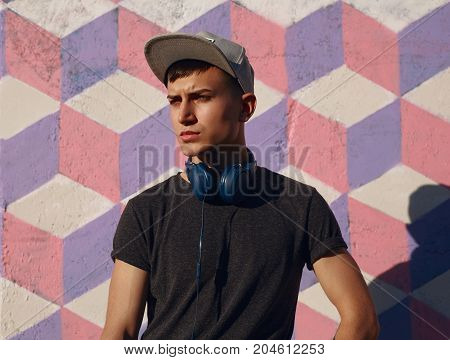 Portrait of young confident man in casual clothing posing with big headphones on neck looking away.