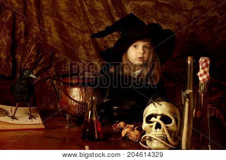 Little caucasian girl in with costume with Halloween objects on the table