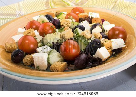 mediterranean salat with black olive grape goat cheese and croutons on a plate