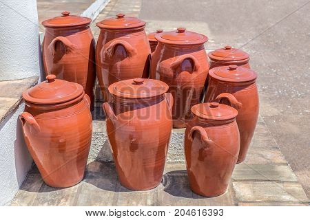 Group of clay pots on floor outside pottery