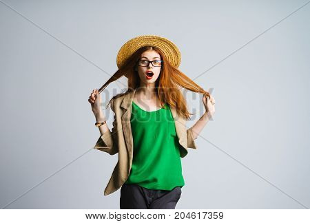 Surprised beautiful fashionable woman in a hat, facial expression of a surprise. Holds hair, glasses