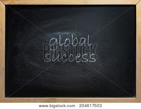 Global Success text written on black school board with wooden frame.