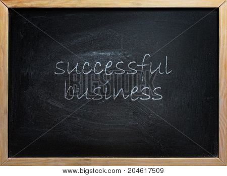 Successful Business text written on black school board with wooden frame.