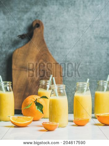 Healthy yellow smoothie with citrus fruit and ginger in bottles on light marble table, wooden board and grey wall at background, selective focus, copy space. Clean eating, vegan, dieting food concept