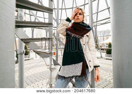 A tired young woman in the street holds her head and waits for someone on the street