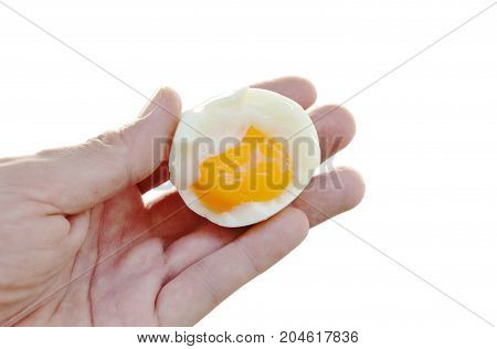 boiled egg half cut with creamy yolk holding on hand in white background