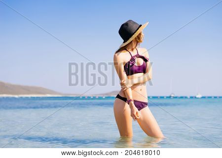 Woman on beach,unrecognisable. in straw hat. Luxury relaxing