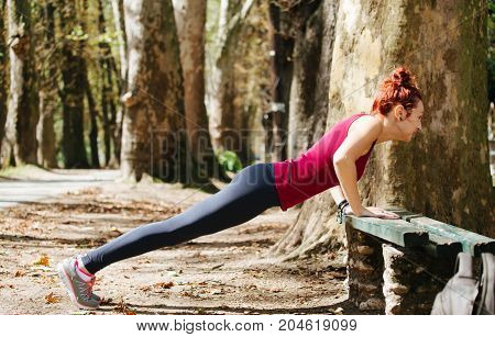 Fitness Woman Doing Feet Elevated Push-ups On A Bench In The Park. Sporty Girl Exercising Outdoors