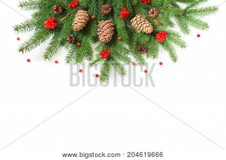 Christmas tree branches with cedar cones and red berries of viburnum as decor on a white background. View from above.