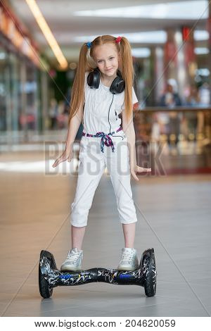Happy And Smiling Girl Rides On Mini Segway In The Headphones At Trading Mall. Teenager Riding On Ho