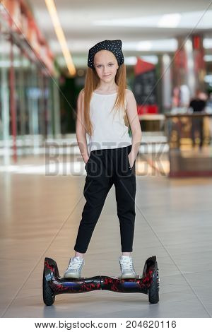 Happy And Smiling Girl Rides On Mini Segway At Trading Mall. Teenager Riding On Hover Board Or Gyros