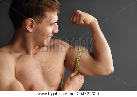 Young cheerful sportsman posing without shirt and measuring muscular bicep with tape on gray background.