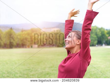 Portrait of an excited woman with eyes open raising arms skyward outdoors