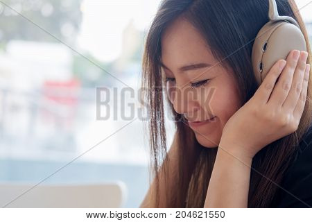 Closeup image of a beautiful Asian woman enjoy listening to music with headphone in modern cafe with feeling relax and happy