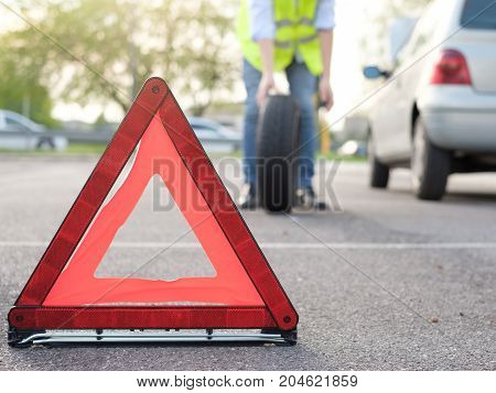 Man Changing One Flat Tyre After Vehicle Breakdown