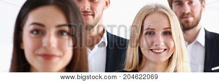 Group Of Smiling People Stand In Office Looking In Camera