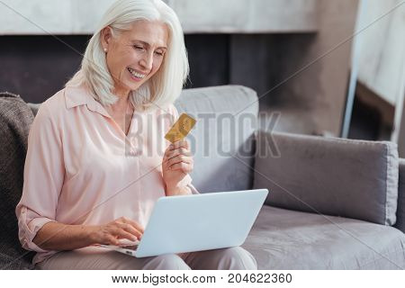 Purchase online. Waist up of a cheerful retired woman holding her credit card and using her laptop while enjoying online shopping