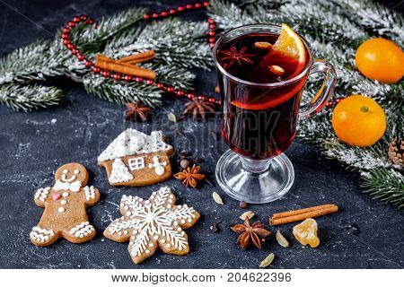 Christmas mulled wine with spices in cup on dark background clos