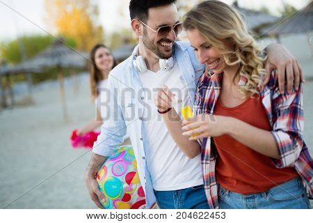 Young happy people having fun at beach in summer