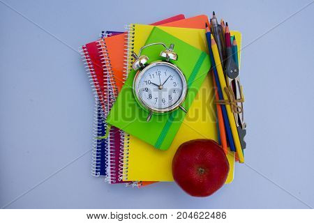 back to school concept - alarm clock and school supplies on blue background