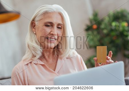 Come in handy. Cheerful smiling aged woman sitting at home and using her laptop while holding her credit card