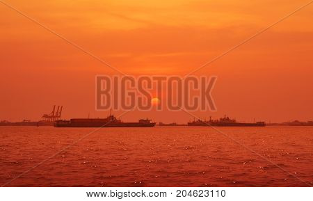 Cargo ship with shipping port over sunset sea