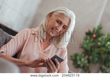 Text me. Cheerful beautiful old woman holding her smart phone and chatting while resting on the couch