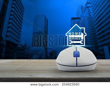 Hammer and wrench and house icon with wireless computer mouse on wooden table over modern office city tower Home service concept