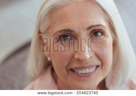 Open minded look. Close up of a cheerful pleasant senior woman smiling and looking at you while posing in front of the camera