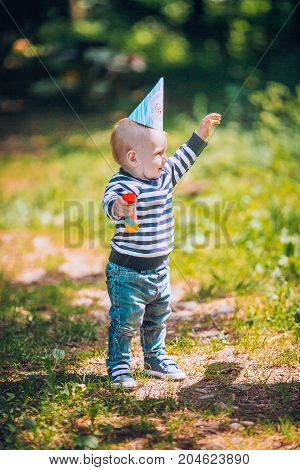 Cute child baby boy lying on blanket in summer day on nature. Happy smile, 1 year old, outdoor. Family picnic in a park.