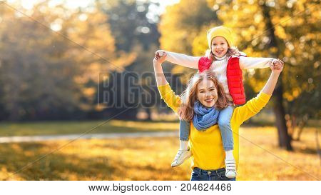 happy family mother and child daughter playing and laughing on autumn walk