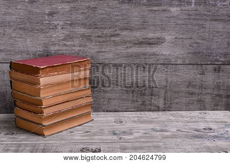 A Stack of old books on a vintage table. Copy space.