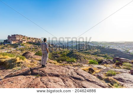 Tourist Standing On Rock And Looking At Expansive View Of Jodhpur Fort From Above, Perched On Top Do