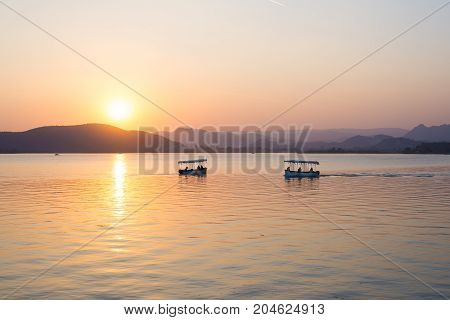 Boats Floating On Lake Pichola With Colorful Sunset Reflated On Water Beyong The Hills. Udaipur, Raj