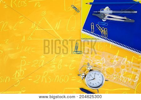 back to school styed scene with blue and yellow school supplies on yellow background with math formulas