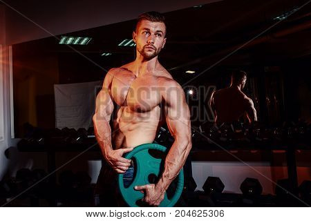 Muscular Strong Athletic Men Pumping Up Muscles And Training In Gym. Handsome Bodybuilder Guy Doing