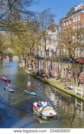 UTRECHT, NETHERLANDS - APRIL 09, 2017: Tourists taking a tour through the historic canals of Utrecht in a paddleboat and paddle boards