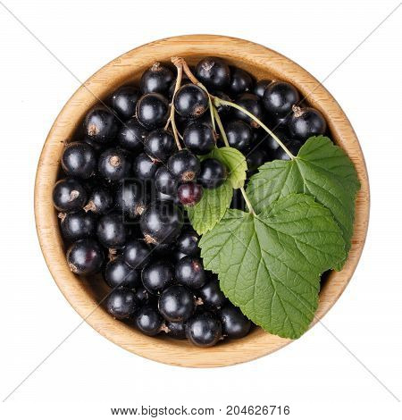 Black currant berries in wooden bowl isolated on white background. Top view.