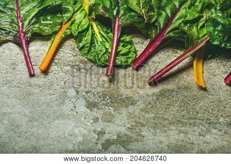 Flat-lay of fresh leaves of swiss chard over concrete stone background, copy space, horizontal composition. Food frame. Clean eating, vegetarian, alcaline diet, organic, healthy cooking concept