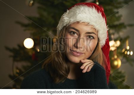 Smiling brunette at Christmas time in Santa hat portrait