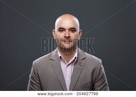 Portrait of a bald affable man in a suit against a dark background, studio shot.