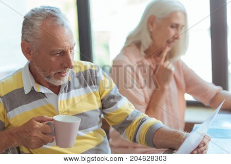 Get informed. Positive delighetd aged man drinking tea and reading a newspaper while his nice wife sitting in the background