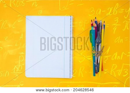 back to school concept minimalistic and creative scene with copy space on empty sheet on yellow background with math formulas