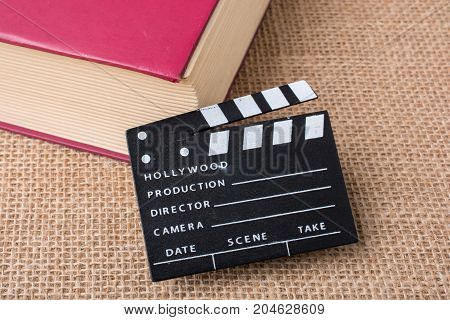 Movie Clapper Beside A Book On A Canvas