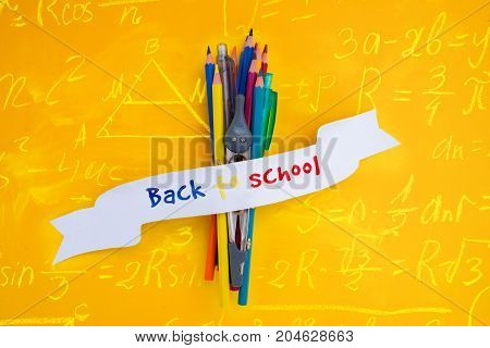 school supplies with back to school text on ribbon with math formulas